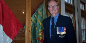 Major Tony Keene standing in front of the Grey & Simcoe Foresters Regimental Colours in the Officers' Mess at the Barrie Armoury.  Photo:  Bruce Forsyth.