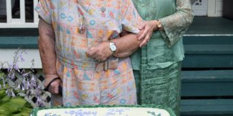 """L-R:  Luella Macdonald Veijalainen and her grandmother, """"Lucy Maud Montgomery"""", prepare to cut the 24th anniversary cake for Bala's Museum, July 2016.  Photo:  Bruce Forsyth."""